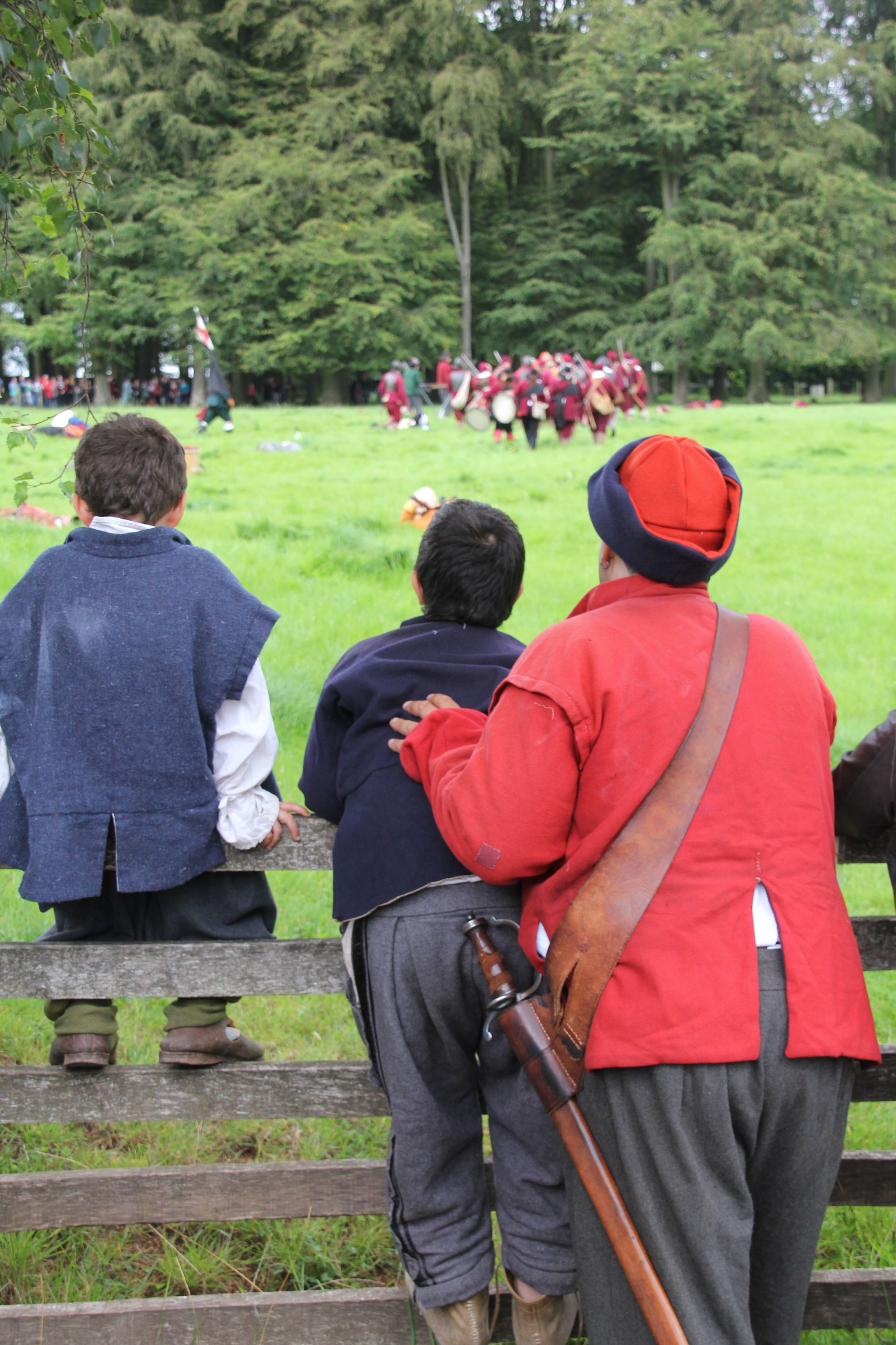 Older and younger re-enactors watch a battle display