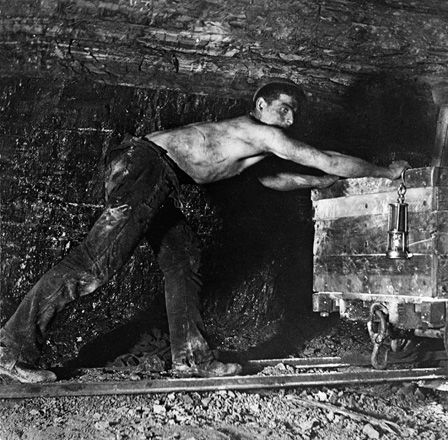 Worker pushing a cart in a mine