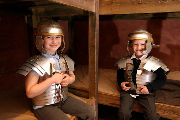 two boys dressing up in roman armour