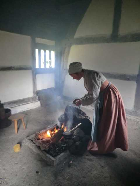 A woman dressed in 1530s style adds spices to a cauldron