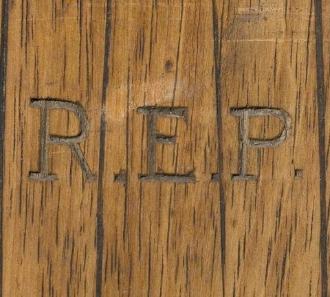 The initials of Raymond Edward Priestley are carved into each ski.