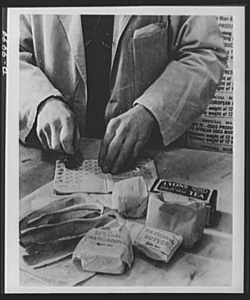 A shopkeeper cancels the coupons in a British housewife's ration book for the tea, sugar, cooking fats and bacon she is allowed for one week. Most foods in Britain are rationed and some brand names are given the designation