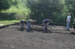 Four students use mattocks to start a new trench.