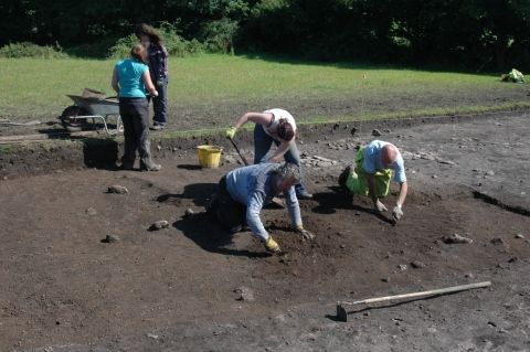 Two archaeologists use trowels to gently uncover archaeology. Assistants remove the waste