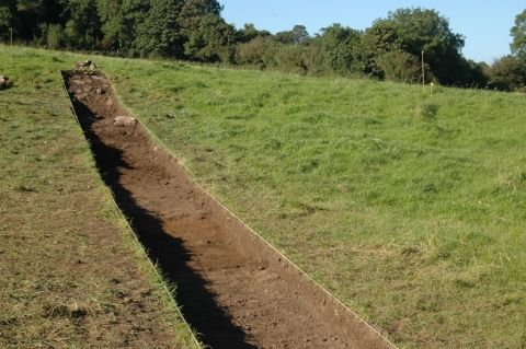 Changes in soil colour show two ditches crossing this trench
