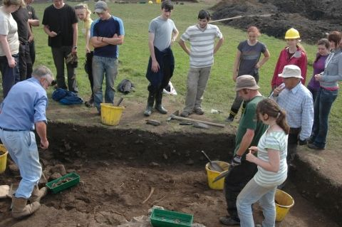 An excited team gather to view a human bone as it starts to emerge from the soil