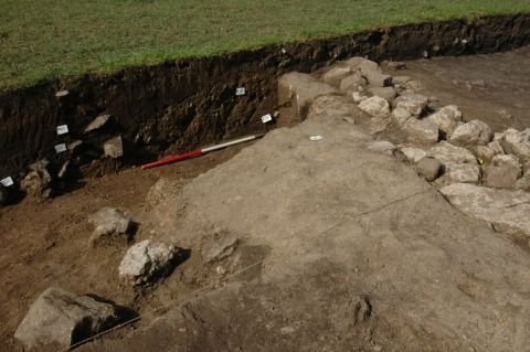 In the trench, a wall of limestone blocks is seen. A change in soil texture and colour in the cut of the trench reveals a cross-section of the early medieval ditch. Labels mark significant finds