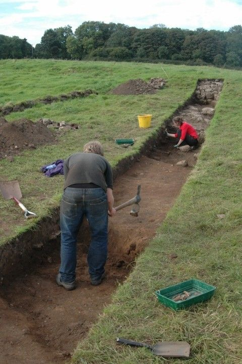 A long, narrow trench. A student uses a trowel to define the edge of one of two early-medieval defensive ditches which cross the trench, visible by changes in soil texture and colour. Another student mattocks away excess topsoil from the other ditch