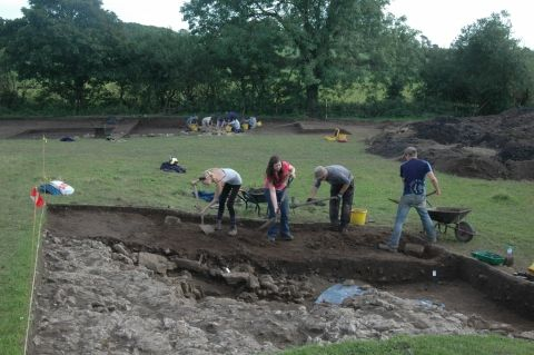Four students use mattocks and shovels to remove the topsoil. Trowels will be used once archaeology is reached
