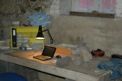 A table is set up in a barn. It holds a light, laptop and various finds. Some are stones, marked with a finds label. Others are in labelled bags. Some bags have been put into boxes to give them extra protection. The boxes are labelled glass, copper alloy,