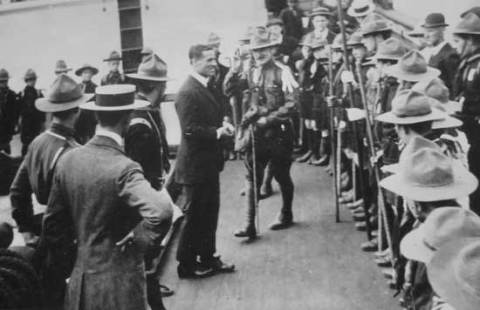 Commander Evans returns the flag to Scoutmaster T.W. Harvey on board the <em>Terra Nova</em> on 17 June 1913.