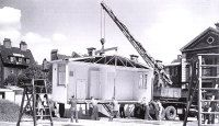 An aluminium prefab prototype being installed, ready for exhibition, outside the Tate Gallery in London, 1945. Crown copyright NMR