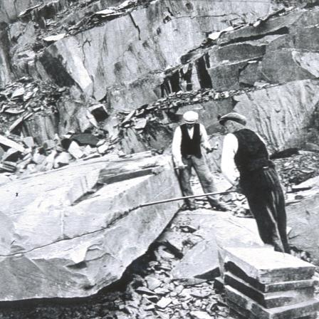 Quarrymen splitting a large block of slate in the Dinorwig Quarry, about 1920.