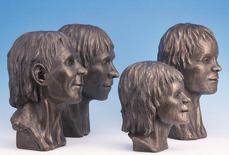 Four of the five faces from Llanbedrgoch, cast in brass.