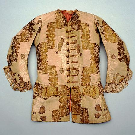 Man's short coat, dating to the early 1720s. The fabric is white taffeta with a lace pattern.