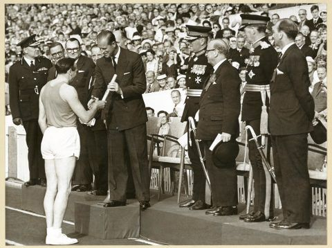 Ken Jones, former Wales rugby player and Olympic athlete, presenting the baton to the Duke of Edinburgh at the opening ceremony at Cardiff Arms Park. (© Commonwealth Games Federation)
