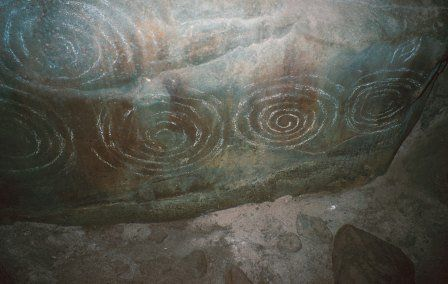 Carved stone inside the chamber of Barclodiad y Gawres (Anglesey). The style of carving in this passage tomb is common to many tombs in Ireland.
