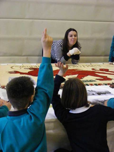 Elen Phillips exploring the Suffrage collection with children from Ysgol Gymraeg Casnewydd