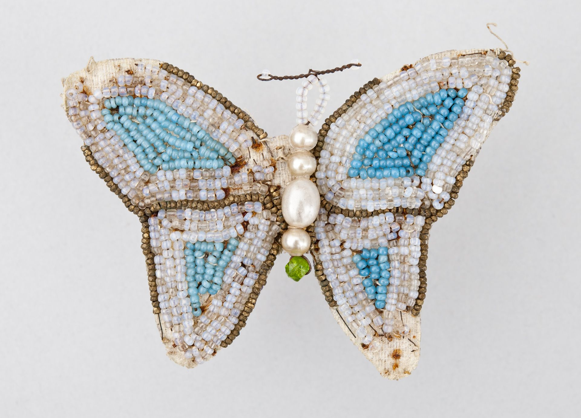 Butterfly shaped cotton belt buckle, decorated with wire and glass beads.