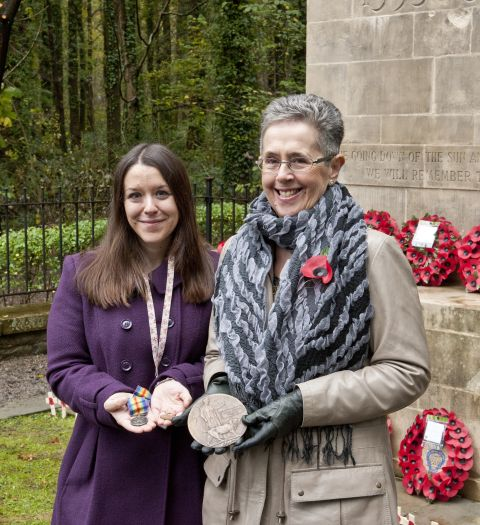 Mrs Gaynor Hoare (left) presenting Alfred Prosser Workman's campaign medals and memorial plaque to the Museum, November 2014. She is holding the medals in her hand in front of the Newbridge War Memorial.