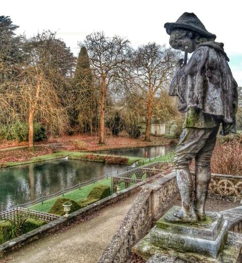 A picture of a statue of a piper over looking St Fagans ponds