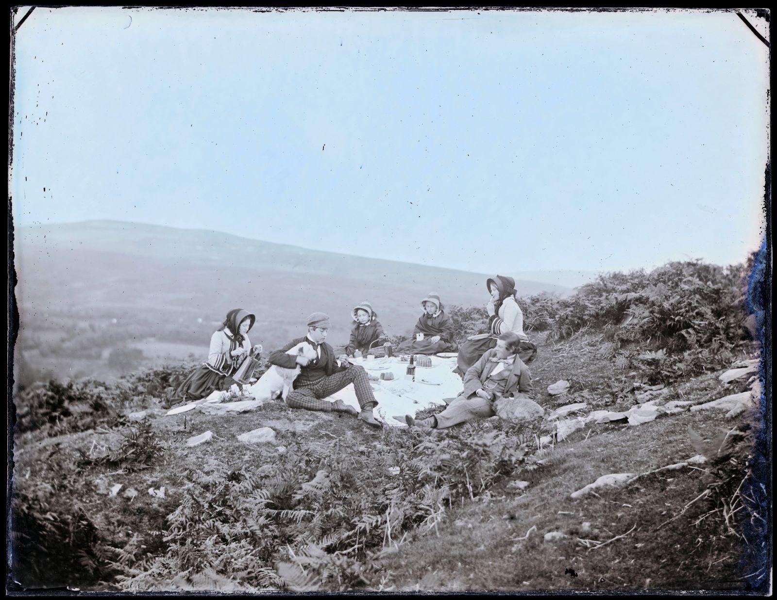 This photographs shows the Llewelyn children having a picnic on the Goppa near Swansea in 1855. It is one of a series of photographs of the children taken by John on the 23rd September each year for his wife's birthday.