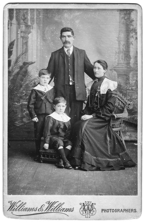 Studio portrait of the Edmunds family in about 1905. The father stands behind his wife and two children.