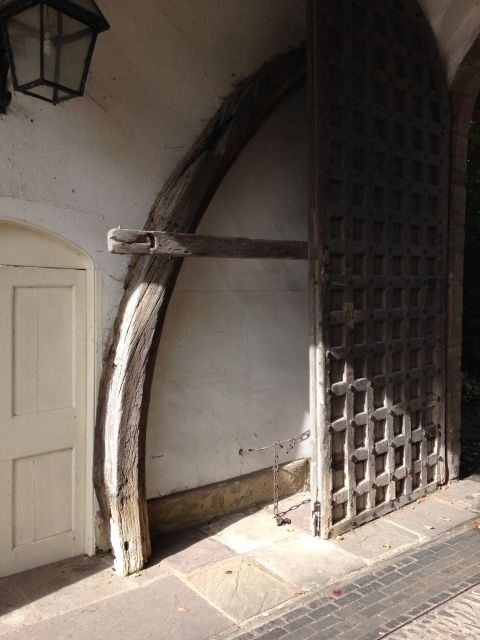 A wooden arched brace leaning against the wall of a porch