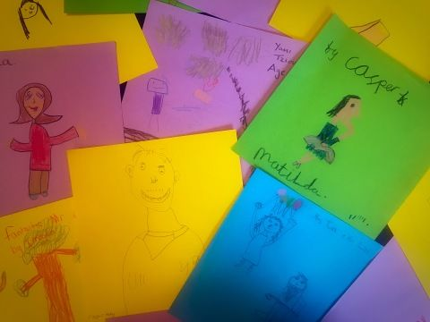 A collection of drawings by children on colourfull paper.