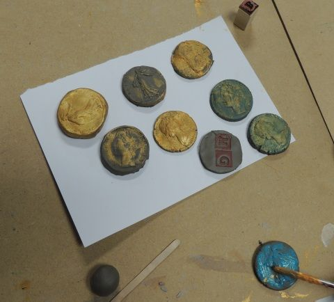 Some coins made out of modelling clay and painted with gold paint made at a children's workshop.