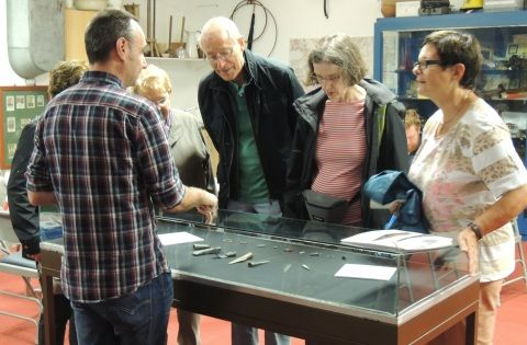 People are gathered around a small display case of objects acquired for Swansea Museum.