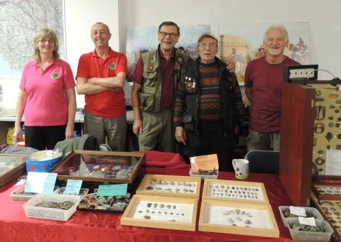 Members of the Heritage Metal Detecting Club, Swansea, are standing behind a display of some of their finds.