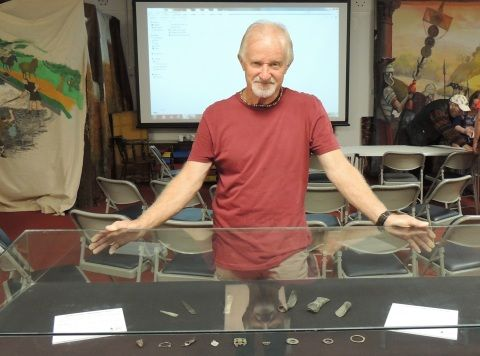 A man stands behind a small display case of several small metal objects including Bronze Age tools.