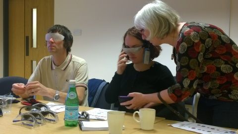 Two members of Museum staff wearing simulation spectacles counting out coins from a purse, overseen by the course trainer Sian
