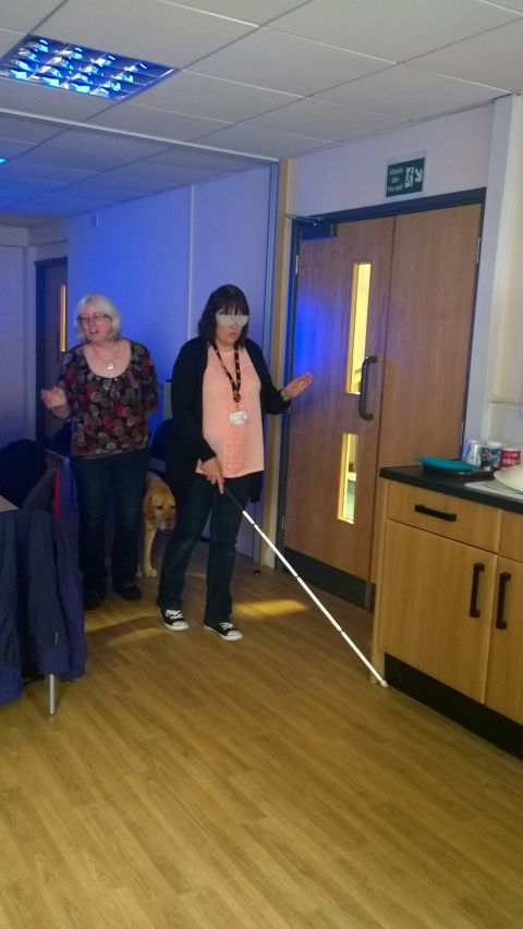 A female member of Museum staff, blindfolded and using a cane to walk around the office