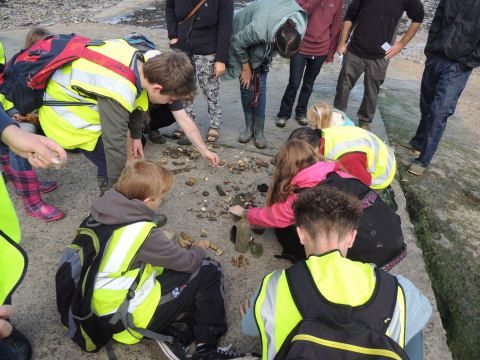 Some children are sorting out pieces of pottery and metalwork on the floor