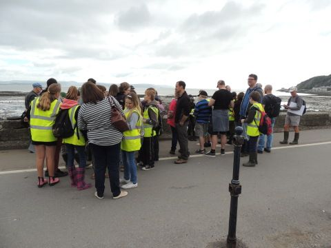 A large group of people gather at the side of the road before going on to the beach.