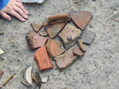 A collection of broken pieces of pottery is laid out on the floor