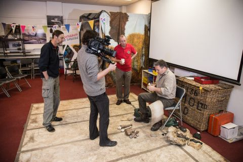 A cameraman is filming the flint knapper at work.