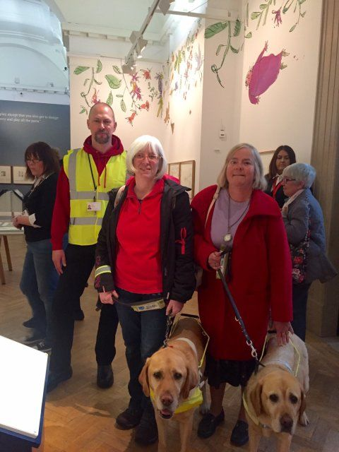 Photograph of two ladies with guide dogs and a member of museum staff