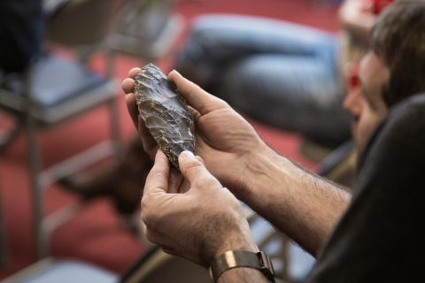 A man holds a piece of worked flint