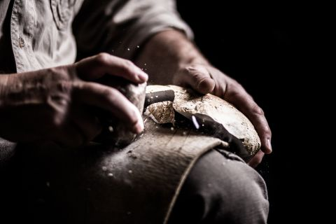 Close up of a man shaping a piece of flint with an antler