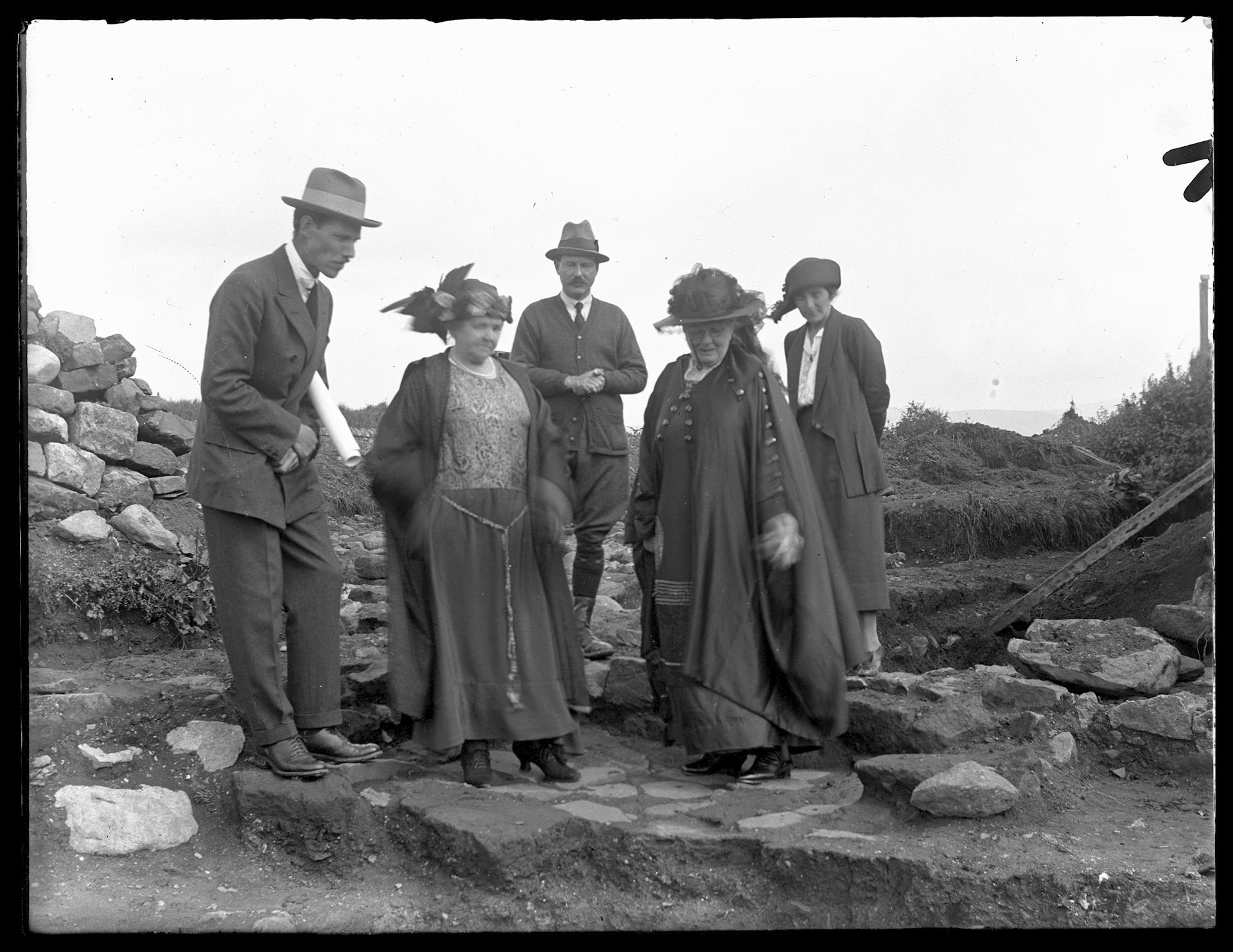 Black and white photograph of group of people visiting excavations