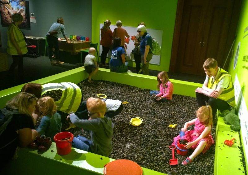 Photograph of children and museum staff playing in the dinosaur dig pit in the dinosaur babies exhibition