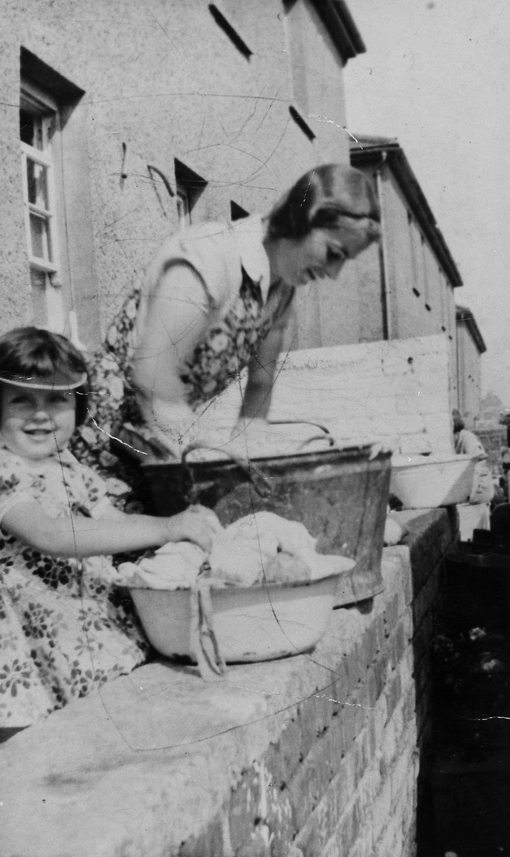 Image of woman and child washing clothes in a zinc bath on the garden wall at Pyle, Mid Glamorgan, 1930s.