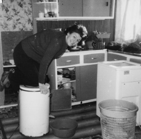 Mrs.Evelyn Potter, Taffs Well  coping with the electric spin drier by kneeling on top of it in the 1970s.