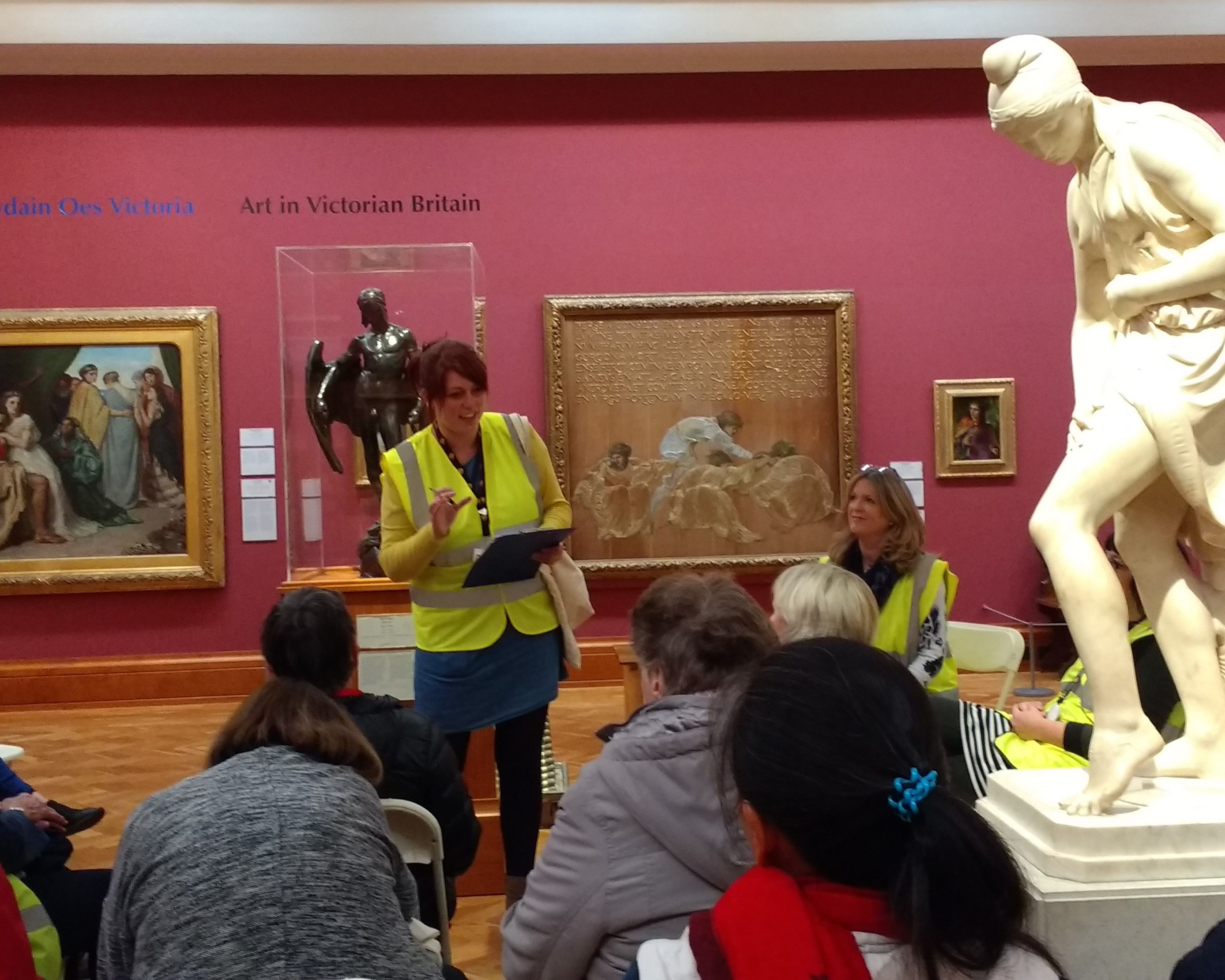 A crowd of people sitting in the Victorian Art gallery at National Museum Cardiff, listening to a tour guide