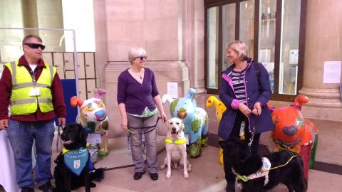 Three Guide Dogs and their owners standing next to the Snowpup sculptures at National Museum Cardiff