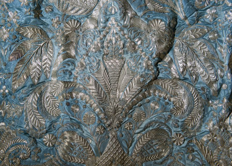 Section of blue damask fabric with intricate silver thread embroidery