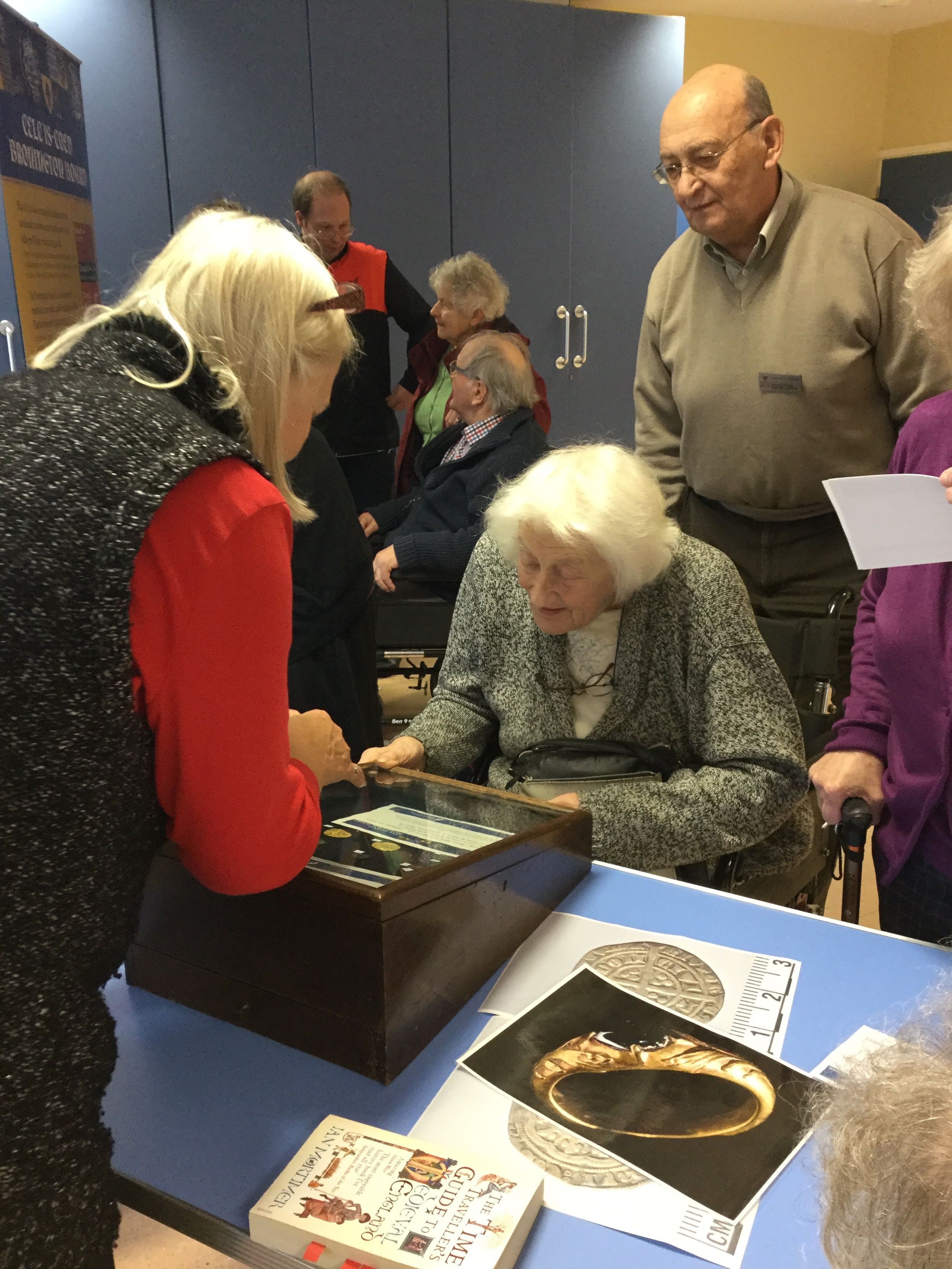 People discussing a display of coins.